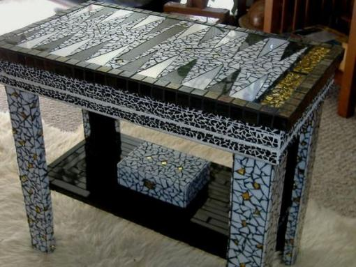 A stained glass backgammon table with intricate colored glass pieces from a recycled table.