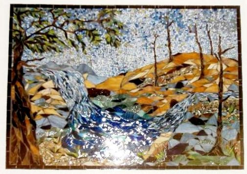 A stained glass portrait art of a waterfall scene on a piece of scrap wood.
