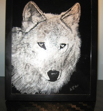 An animal engraving of a wolf in glass.
