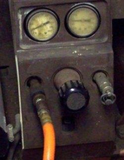Adjustment gauges on compressor for air pressure settings.