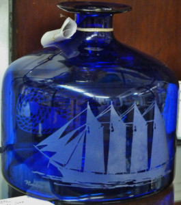 A blue glass jug etched with an old ship.