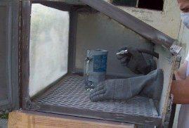 Sandblast etching process inside abrasive cabinet.