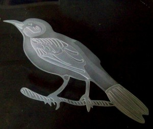 A 2 stage sandcarved bird in glass.