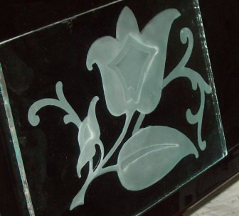 Three stage glass sandcarving project of a flower.