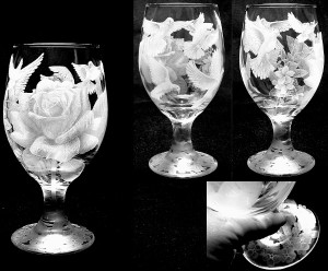 A flower and multiple doves shade engraved into a glass.
