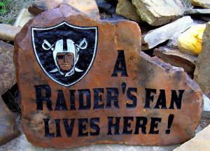 A fun Oakland Raiders fan engraves a design in rock.