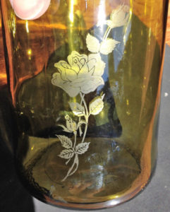 A rose etched on a cut glass wine bottle.