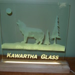 Sandblasted glass led sign with a wood stand and etched wolf.
