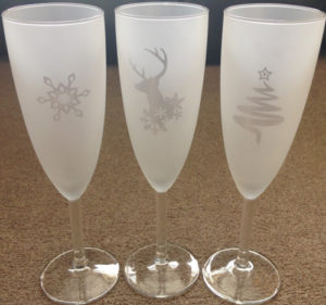 A Christmas tree, reindeer and snowflake reverse (negative) etched on Champagne glasses.